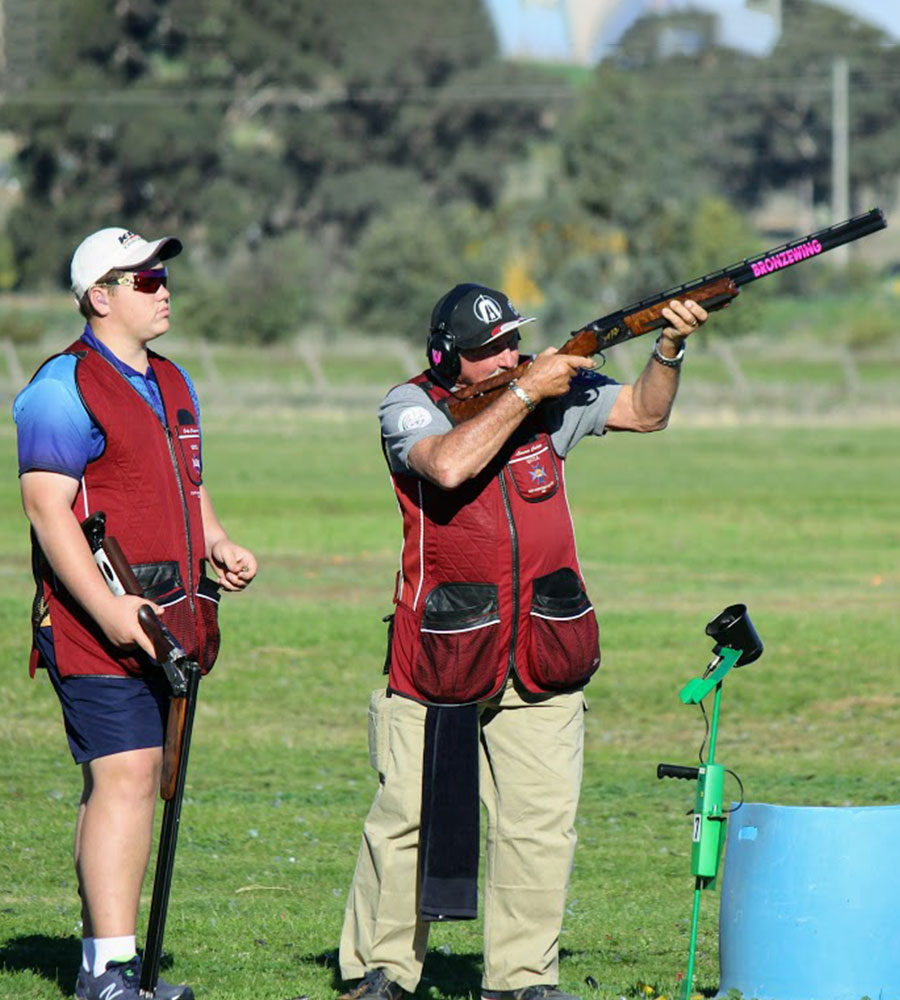 Clay target shooting - shooter taking aim with helper