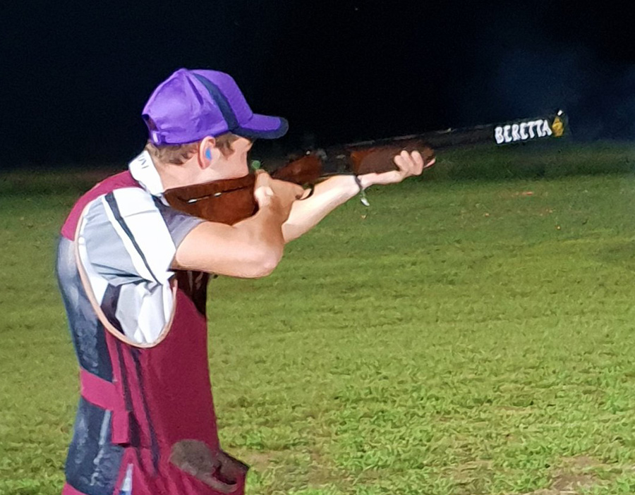 Clay target shooting - shooter taking aim in a night clay target shoot